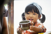 Close Up Of Young Girl With Black Pigtails And Blue Hairband Holding A Ceramic Bowl.