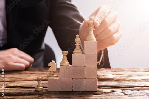 Fotografie, Obraz  Businessperson Arranging Chess Piece On Wooden Blocks