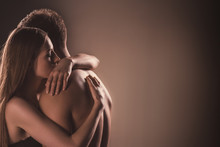 Sensual Nude Couple Embracing With Closed Eyes, On Brown