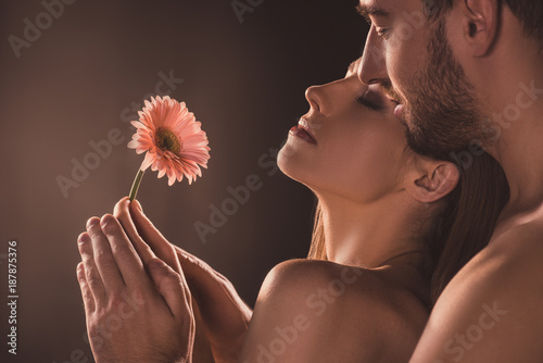 naked sensual lovers holding flower, on brown Canvas-taulu