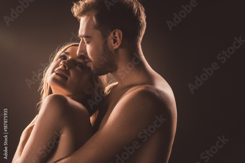 happy naked lovers hugging and looking at each other, on brown
