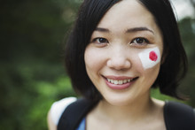 Portrait Of Young Woman With Black Hair, Japanese Flag Painted On Her Cheek, Smiling At Camera.
