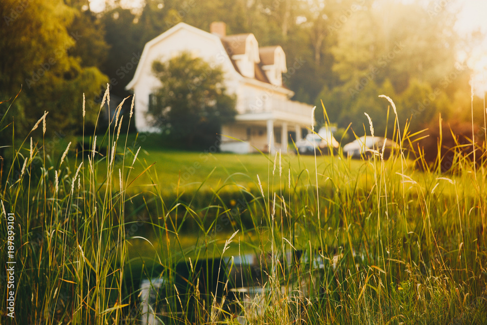 Fototapeta rural view, blurred background. pond and house in the distance at sunset