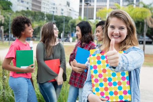 Photo Blonde Studentin zeigt Daumen auf Campus