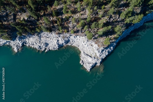 Foto op Aluminium Zee / Oceaan Rocky cliff and trees along the turquoise sea