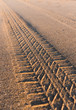 Tyre tracks going off in the distance on a golden sandy beach at sunset