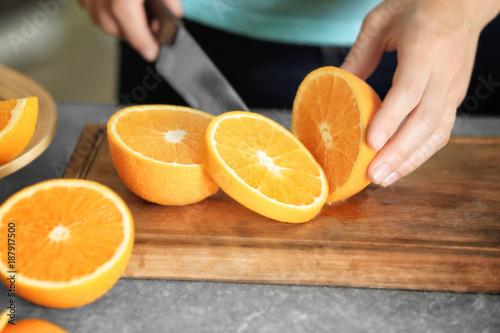 Woman cutting orange on board in kitchen
