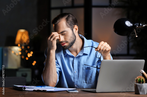 Fotografie, Tablou  Tired young man using laptop in office at night
