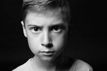 Upset Little Boy On Dark Backg...
