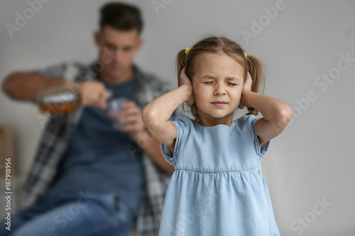 Poster de jardin Bar Little girl covering ears and her father drinking alcohol on background