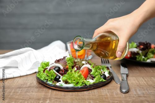 Kobieta dodaje smakowitego jabłczanego ocet sałatka z warzywami na stole
