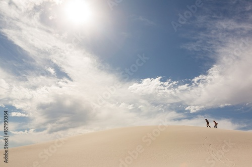 Couple with sandboard walking in sand dune