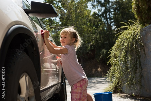 Girl washing a car outside the garage on a sunny day