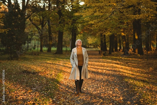 Thoughtful senior woman in jacket looking up in the autumn