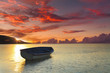 Boat on a tropical beach in the background of a beautiful sunset