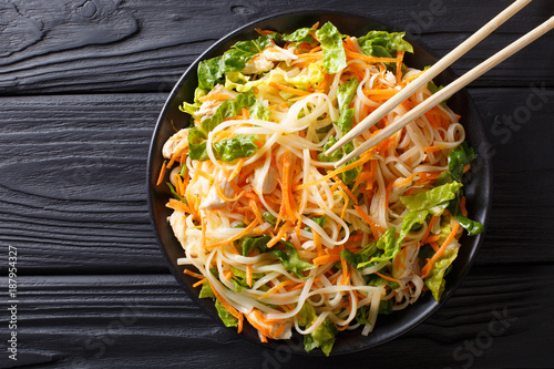Vietnamese chicken salad with rice noodles, carrots and herbs macro. horizontal top view