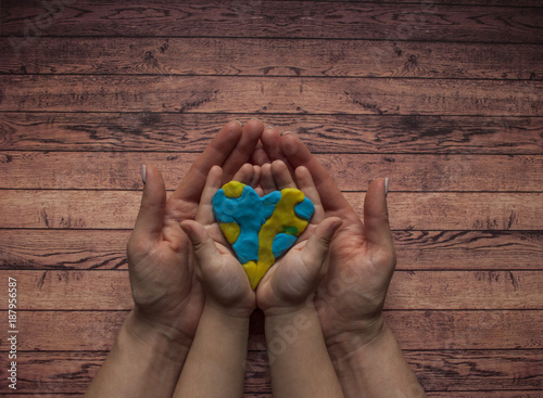 Fotografie, Obraz  Woman's and child's hands holding a heart of blue and yellow color of world Down syndrome Day