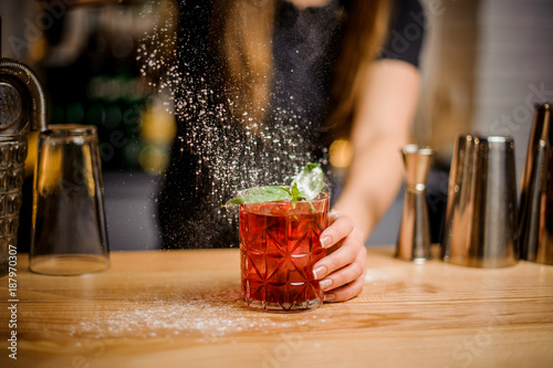 Fotografia, Obraz  blondy barmaid finishes preparation of cocktail by adding a bitter of powdered s