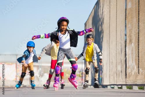 Cute African girl rollerblading at stadium