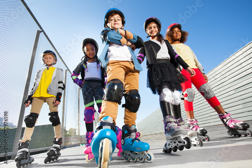 Boy in rollerblades standing with friends outdoors