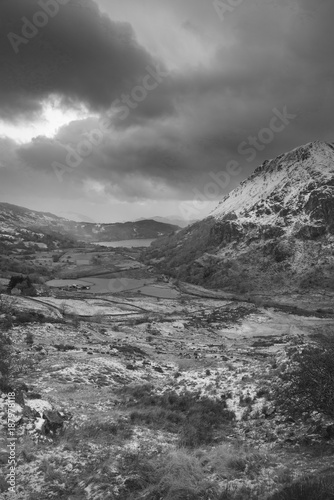 Poster Donkergrijs Beautiful black and white Winter landscape image in Llyn Gwynant in Snowdonia National Park with snow capped mountains in background