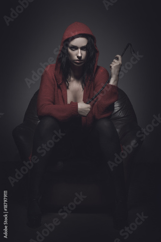 Little red riding hood with whip sitting on sofa Fototapet