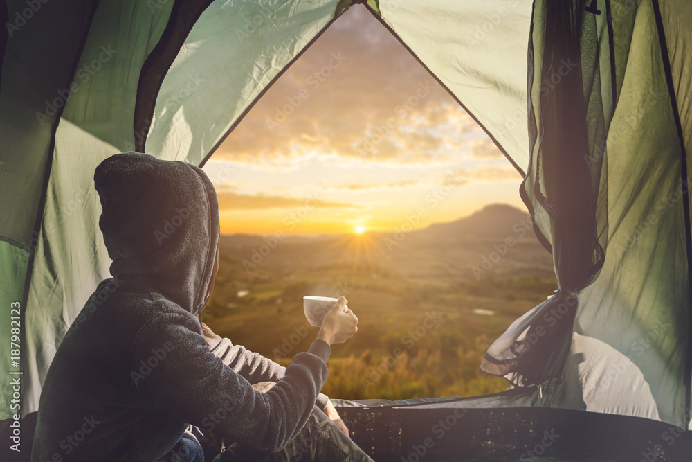 Fototapeta Young woman traveler sitting in the tent, relaxing and drinking coffee with beautiful sunrise