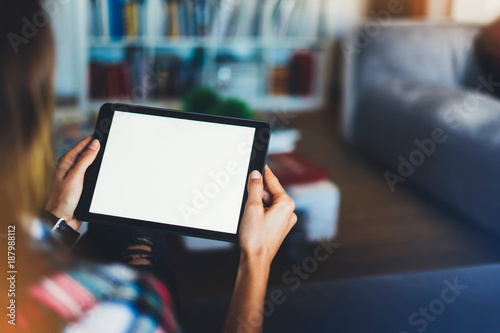 Hipster girl using tablet technology in home atmosphere, girl person holding computer with blank screen on background bokeh, female hands texting on relax holiday, mockup templates gadget