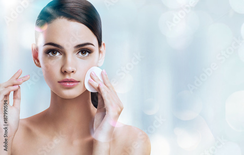 Obraz Young brunette girl removing makeup from her face. Photo of beautiful girl with cotton pads  on shiny silver background. Skin care and beauty concept. - fototapety do salonu