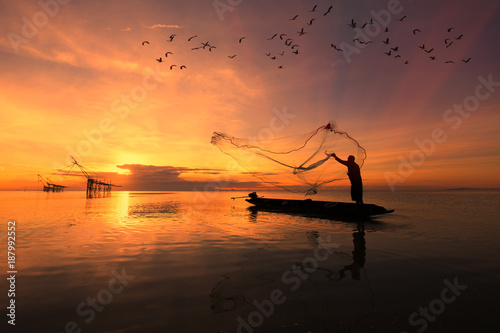 Foto auf AluDibond Rotglühen Asian fisherman on wooden boat casting a net for catching freshwater fish in nature river in the early morning before sunrise
