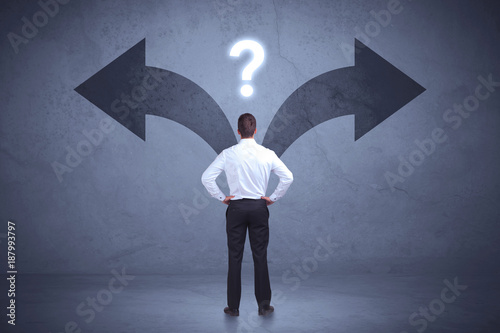 Businessman taking a decision while looking at arrows on the wall concept