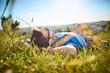 Leinwandbild Motiv Man lying in grass on hiking trip in the mountains