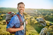 Portrait Of Cheerful Man With Backpack During Hiking Trip In The Mountains