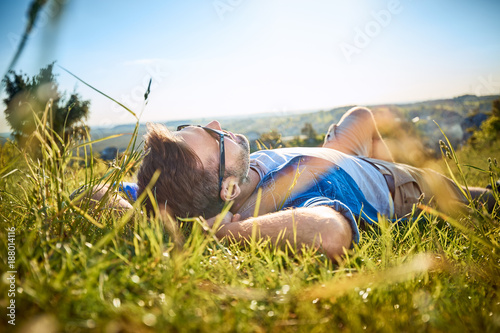 Fotografia Man lying in grass on hiking trip in the mountains