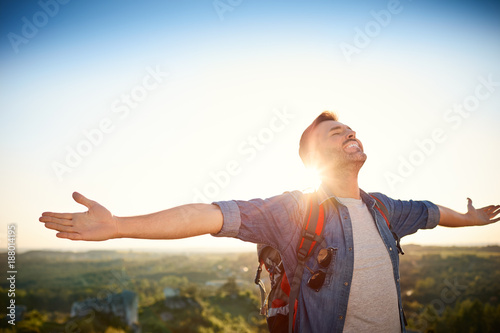 Photographie  Man extending arms and raising head in cheerful gesture during mountain trip