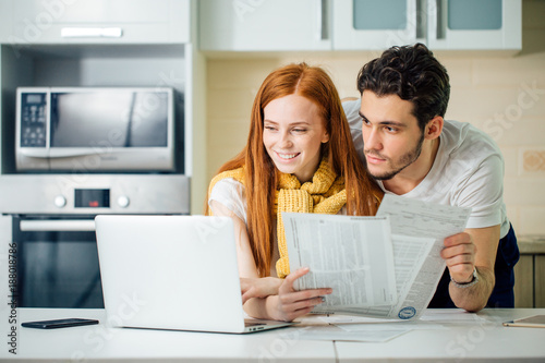 Fotografia, Obraz  Happy couple at home paying bills with laptop and looking screen