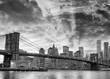 Black and white view of Brooklyn Bridge and Downtown Manhattan at sunset