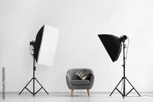 Fototapeta Interior of modern photo studio with armchair and professional equipment obraz