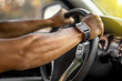 Man who wearing smart watch is driving vehicle while working or going to somewhere with the flare from the outside.