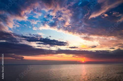 Spoed Foto op Canvas Zee zonsondergang Colorful sunset over calm sea in summer with sun beam