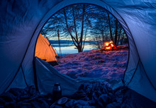 Camp By The Lake With Campfire In Winter At Dusk
