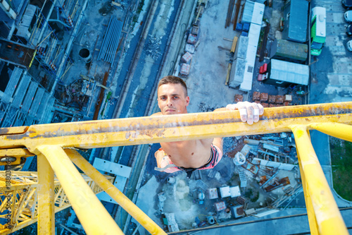 Obraz na plátne Rock climber hanging on jib of construction crane with one hand