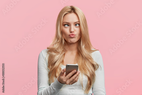 Cuadros en Lienzo Crazy funny comic female crosses eyes, pouts lips, makes grimace, foolishes, holds cell phone, involved in games online, isolated over pink background