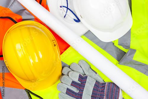 Fotografie, Obraz  Hard safety hats and protective gloves laying on hi vis vests