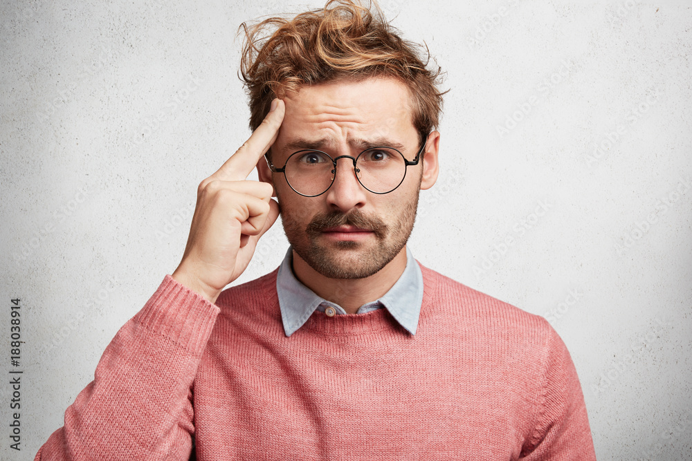 Fototapeta Portrait of handsome young stylish male tries to concentrate as sees something in front, has problematic expression, dressed in pink sweater, has round eyewear, isolated over white concrete wall