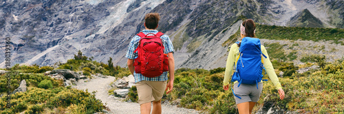 In de dag Kamperen Hikers hiking with camping backpacks walking from behind with bags on outdoor trek in summer nature. New Zealand travel tramping couple on Hooker Valley Track in New Zealand mountains banner.