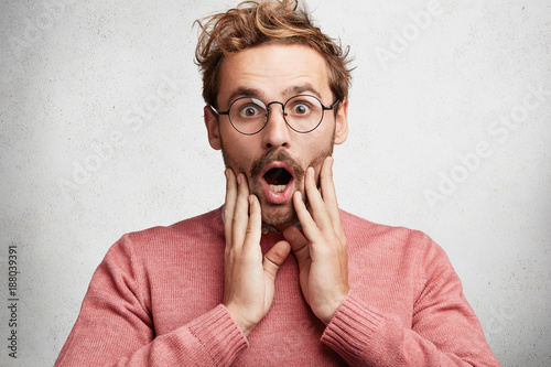 Portrait of amazed astonished male wears glasses and elegant pink sweater, looks with opened mouth, being shocked realize high prices on products, isolated on white concrete wall. Facial expressions