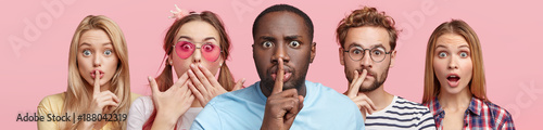 Fototapeta  Horizontal shot of five different people show hush sign, look with stupefied expression, demand complete silence, isolated over pink background