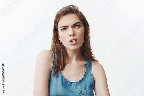 What did you say? Young beautiful dark-haired student girl in blue shirt looking in camera with mean and aggressive expression after hearing offencive words from popular girl in university Canvas Print