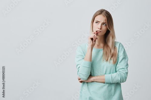 Fotografiet  Beautiful blonde female with puzzled expression, keeps finger on lips, looks aside with bewilderment, poses against gray background